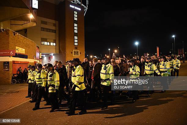 The away fans are escorted by police into the stadium ahead of the UEFA Europa League group A football match between Manchester United and Feyenoord...