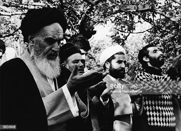 The Ayatollah Khomeini holding his palms up while praying with Iranian government opposition leaders outside his Pontchartrai mansion west of Paris...