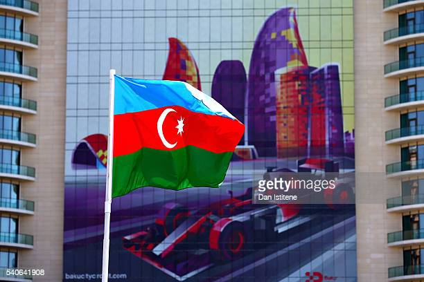 The Azerbaijan flag flies in front of a building with an F1 car graphic on during previews ahead of the European Formula One Grand Prix at Baku City...