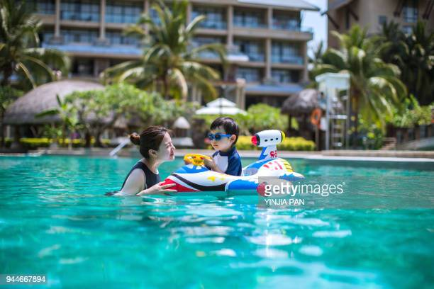 the baby boy playing in the swimming pool with his mother - sanya stock pictures, royalty-free photos & images