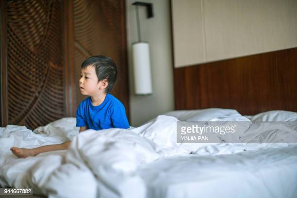 The baby boy sitting on bed after wake up at hotel