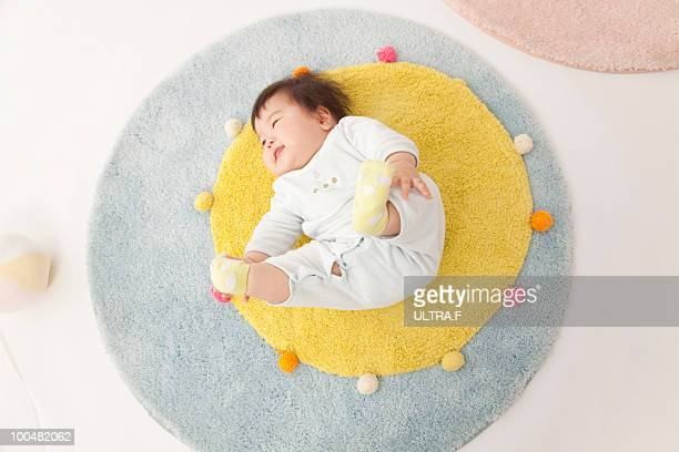the baby is lying down on the floor.  - rug stock pictures, royalty-free photos & images