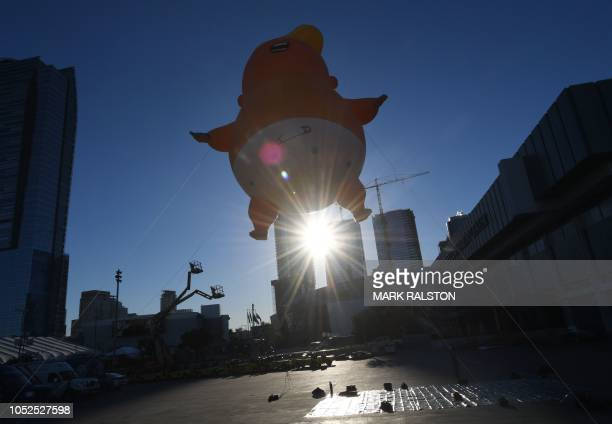 TOPSHOT The Baby Trump balloon flies over the Convention Center as it makes first West Coast appearance during the lead up to the weekends 4th annual...