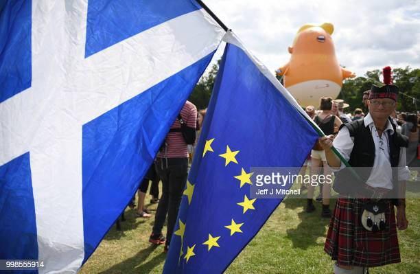 The Baby Trump Balloon floats in the distance as a man dressed in a kilt waves the Scottish Flag and the flag of the European Union while the U.S....