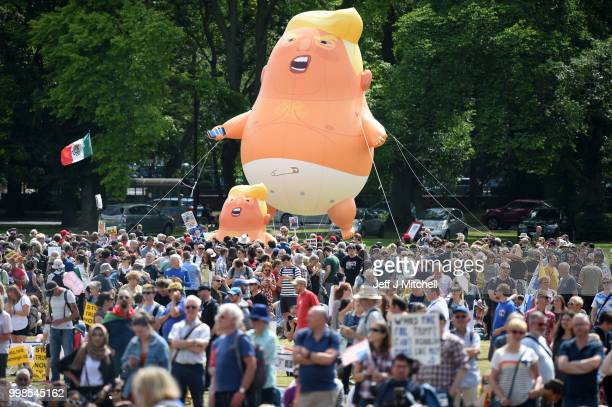 The Baby Trump Balloon floats in the middle of crowds holding antiTrump signs while the US President is visiting Trump Turnberry Luxury Collection...