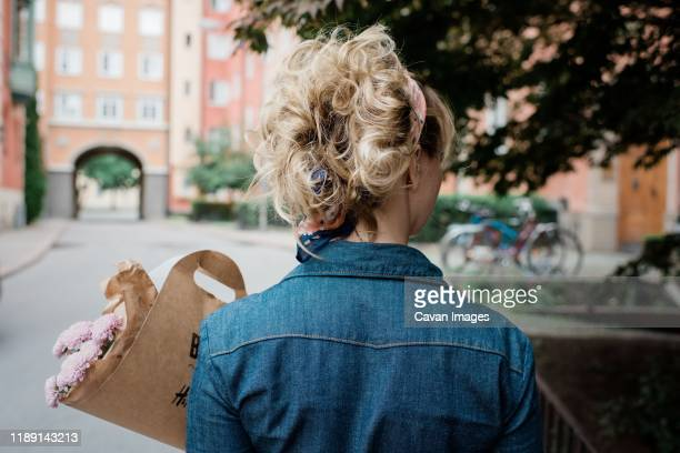 the back of a blonde female holding a bunch of flowers in the street - boyfriend stock pictures, royalty-free photos & images