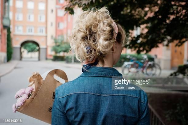 the back of a blonde female holding a bunch of flowers in the street - vriendje stockfoto's en -beelden