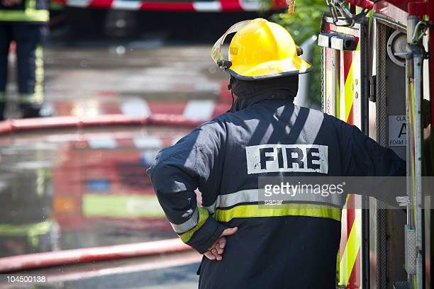 The back of a firefighter leaning against a fire engine