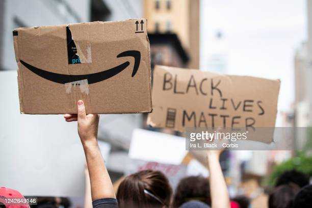 The back of a protesters sign has the Amazon logo next to another protesters sign that says Black Lives Matter Protesters walked from Foley Square to...