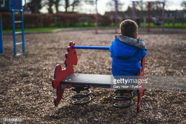 the back of a small boy playing alone in a park looking sad that he is playing alone - portsmouth england stock pictures, royalty-free photos & images