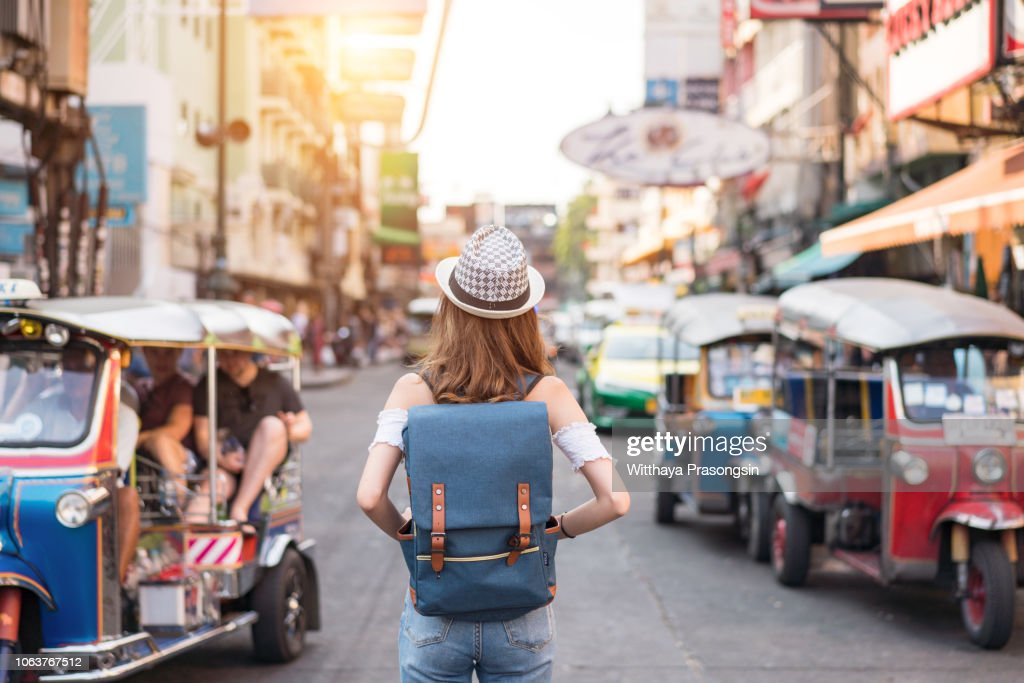 The back of a young woman walking and walking along the pedestrian street in the evening in Bangkok, Thailand, travelers and tourists. : Stock Photo