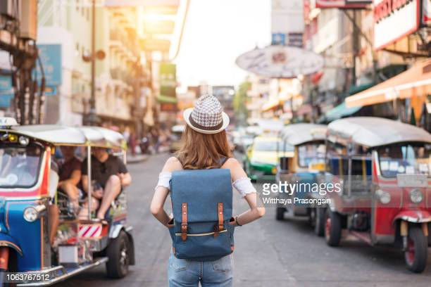 the back of a young woman walking and walking along the pedestrian street in the evening in bangkok, thailand, travelers and tourists. - rucksacktourist stock-fotos und bilder