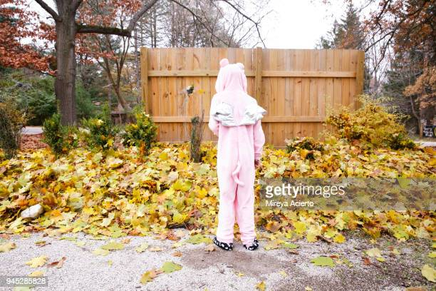 the back of girl wearing pig suit pajamas with silver wings, standing near a stack of leaves. - ann arbor stock pictures, royalty-free photos & images