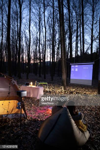 the back of happy couple night camping outdoors - プロジェクター ストックフォトと画像