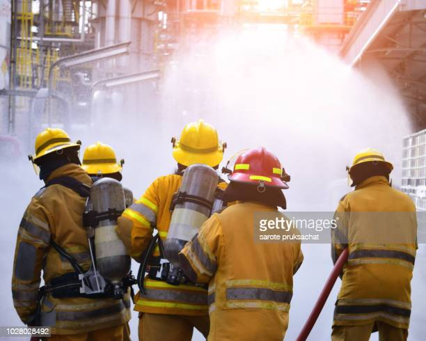 the back side view of a group of firefighters helped stop the fire. fire in the industrial factory . rescue ,teamwork concept . - brigade stock pictures, royalty-free photos & images