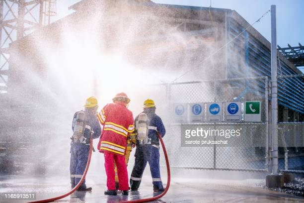 the back side view of a group of firefighters helped stop the fire. - brigade stock pictures, royalty-free photos & images