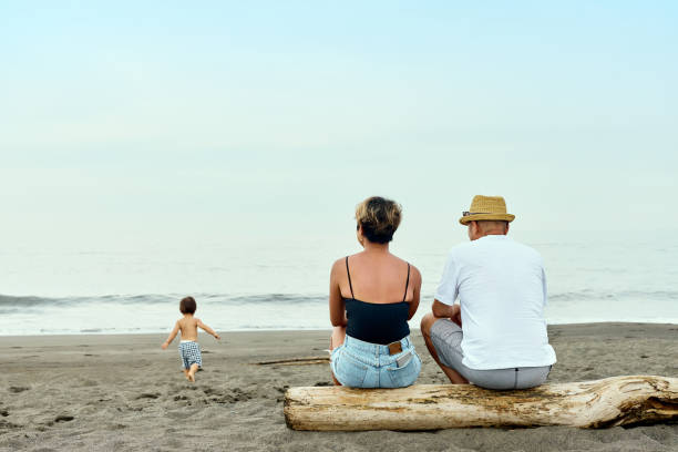 The back view of a couple watching the growth of their children on the beach.