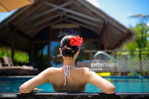 The Back View of Bikini Woman Relaxing In Swimming Pool
