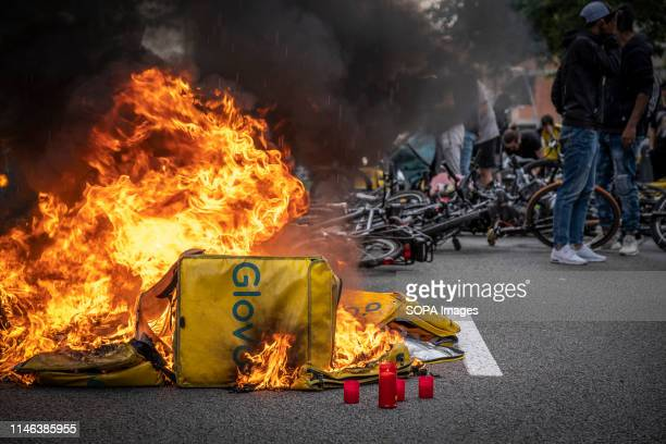 The backpacks of the Glovo delivery cyclists are seen burning during the protest A group of food on demand couriers service workers of the company...