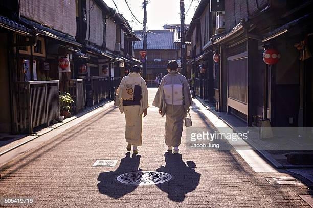 CONTENT] The backs of two women in kimonos walking down a machiya filled street in the traditional Gion district of Kyoto Kyoto Japan May 23 2014