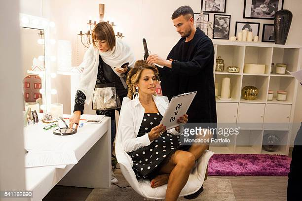 Italian TV presenter Barbara D'Urso sitting in the dressing room reading her notes and adjusting the makeup and the hair Photo shooting Cologno...