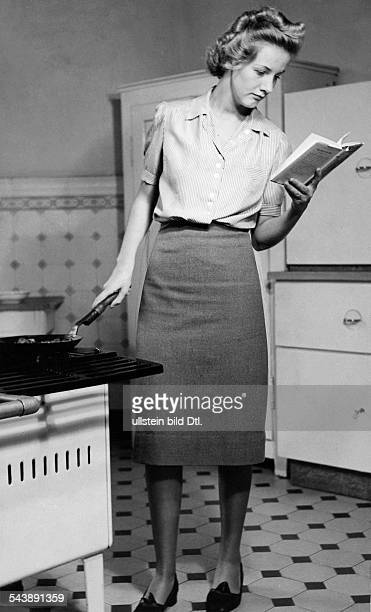 The bad cook woman frying a schnitzel while she is reading a novel Photographer Peter Weller Published by 'Das Blatt der Hausfrau' 16/1939Vintage...