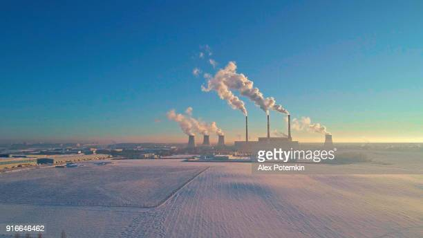 the bad ecology. the thermal power plant near by big city in the cold winter's day. aerial drone photo - minsk stock pictures, royalty-free photos & images