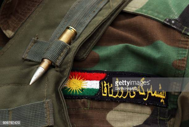 TOPSHOT The badge of SyrianKurdish Peshmerga fighter and member of the Rojava Forces Defence Units is seen as he holds a position in the town of...