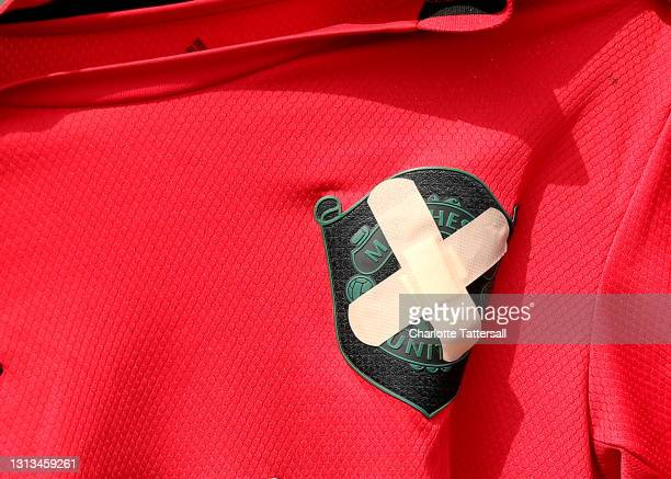 The badge on a Manchester United football shirt is seen covered up with two plasters outside Old Trafford on April 20, 2021 in Manchester, England....