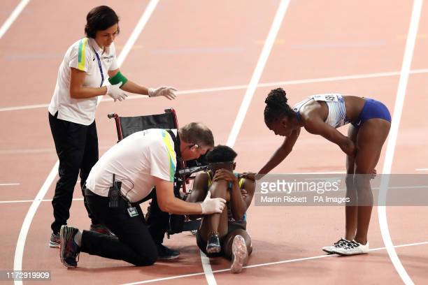 The Bahamas' Anthonique Strachan is comforted by Great Britain's Dina AsherSmith after picking up an injury in the Womens' 200m SemiFinal Heat three...