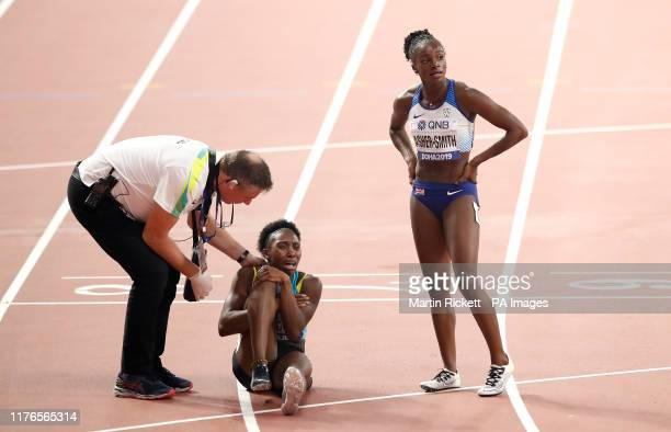 The Bahamas' Anthonique Strachan is comforted by Great Britain's Dina AsherSmith after picking up an injury in the Womens' 200m SemiFinal Heat three