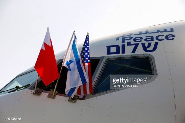 """The Bahraini, Israeli and US flags are picture attached to an air-plane of Israel's El Al, adorned with the word """"peace"""" in Arabic, English and..."""