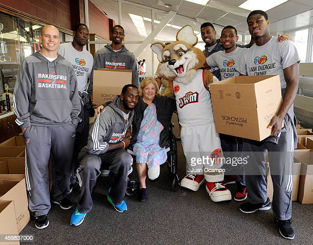The Bakersfield Jam pose for a group photo with a community recipient during the Bakersfield Jam Thanksgiving Box Give Away Event on November 26 2014...
