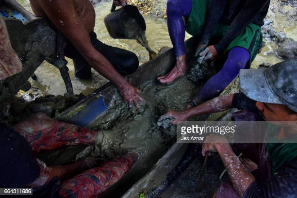 The Balderosdasco family manually dissolving mud with their feet and hands to look for gold on March 22 2017 in Paracale Philippines Apart from...