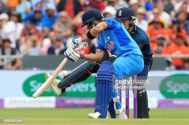 The ball bounces of the pad of England's Jos Buttler as India's captain Virat Kohli plays a shot during the third One Day International cricket match...