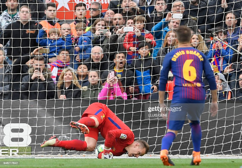TOPSHOT - The ball gets away from Barcelona's German goalkeeper Marc-Andre Ter Stegen to concede a goal during the Spanish league footbal match between FC Barcelona and Valencia CF at the Camp Nou stadium in Barcelona on April 14, 2018. /