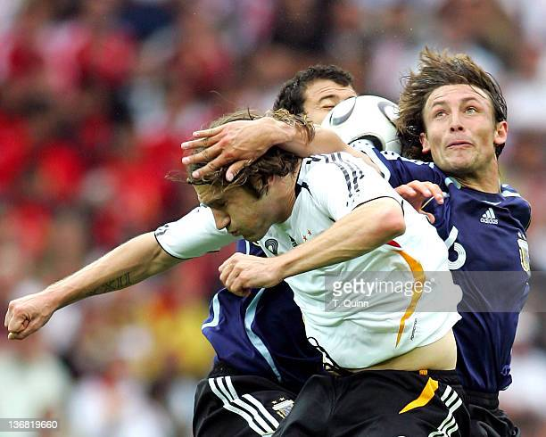The ball gets caught between Torsten Frings of Germany and Gabriel Heinze and Juan Riquelme of Argentina during their quarterfinal match at the...