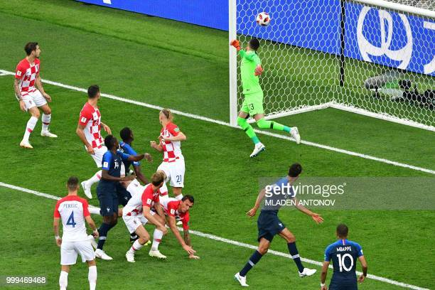 TOPSHOT The ball goes in off of Croatia's forward Mario Mandzukic's head for the opening goal during the Russia 2018 World Cup final football match...