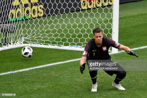 TOPSHOT The ball goes past Poland's goalkeeper Wojciech Szczesny after a shot from Senegal's midfielder Idrissa Gana Gueye was deflected off Poland's...