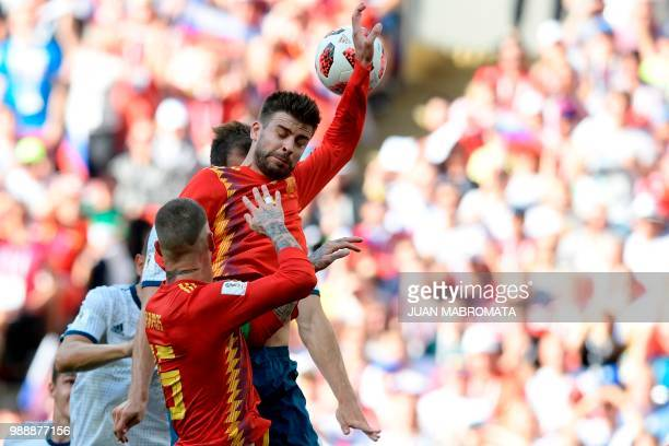 TOPSHOT The ball hits Spain's defender Gerard Pique's hand in the penalty area during the Russia 2018 World Cup round of 16 football match between...