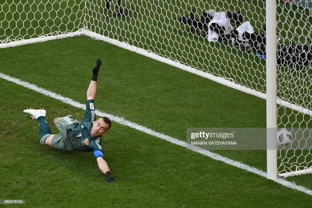 The ball hits the back of the net past Russia's goalkeeper Igor Akinfeev (L) for the opening goal scored by Uruguay's forward Luis Suarez during the Russia 2018 World Cup Group A football match between Uruguay and Russia at the Samara Arena in Samara on June 25, 2018. (Photo by Manan VATSYAYANA / AFP) / RESTRICTED