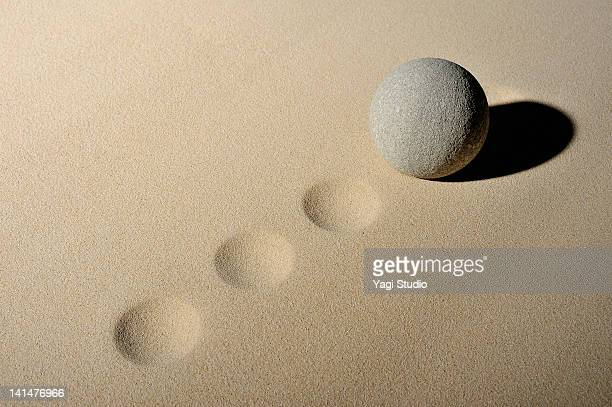 The ball in the sand pit and stone ruins of a sphe