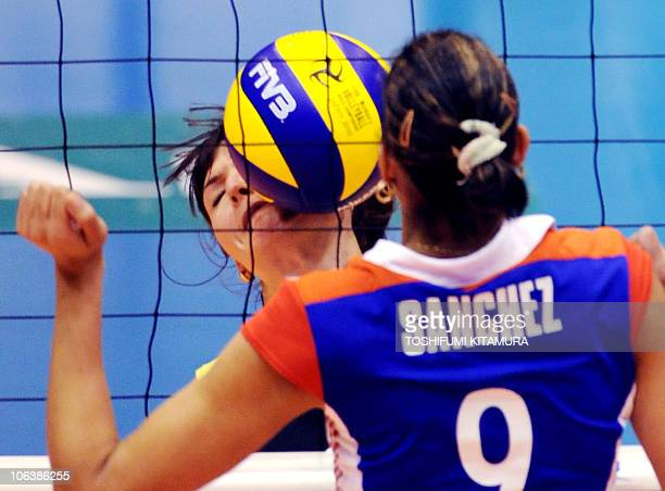 The ball is hit on the face of Kazakhstan's setter Korinna Ishimtseva while Cuba's Rachel Sanchez looks on during their Pool C preliminary round...
