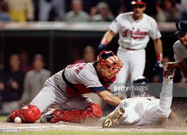 The ball lies by the shinguard of Boston Red Sox catcher Mike MacFarlane as Cleveland Indians baserunner Carlos Baerga slides safely into home to tie...
