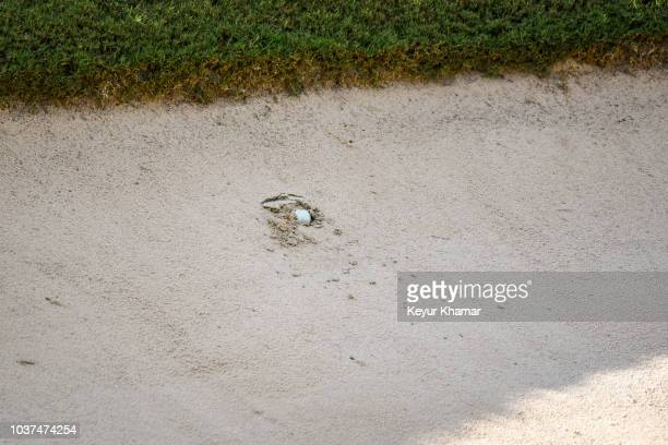 The ball of Tiger Woods sits plugged in a bunker on the 16th hole during the second round of the TOUR Championship, the final event of the FedExCup...