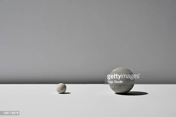 the ball of two stones on white background - stone material stock pictures, royalty-free photos & images