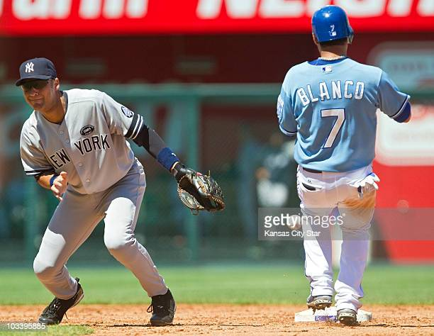 The ball skips past New York Yankees shortstop Derek Jeter for the second error on the play as Kansas City Royals' Gregor Blanco reaches second base...