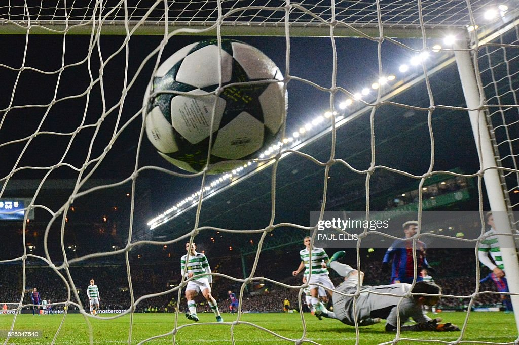 The ball slams into the back of the net after Barcelona's Argentinian striker Lionel Messi (2R) scored a penalty for Barcelona's second goal during the UEFA Champions League group C football match between Celtic and Barcelona at Celtic Park in Glasgow on November 23, 2016. / AFP / Paul ELLIS