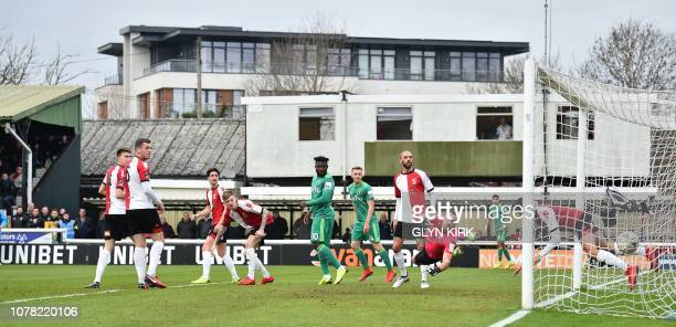 The ball slams into the net from a shot by Watford's English midfielder Will Hughes as Woking's English goalkeeper Craig Ross dives as Watford score...