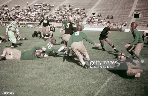 The ballcarrier steamrolls a defender during a high school football game circa 1939.